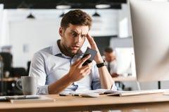 Displeased ha confuso l'uomo di affari che per mezzo dello smartphone e toccando il suo tempio immagini stock libere da diritti