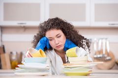 Displeased housewife drying dishes in the kithen Royalty Free Stock Image