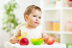 Displeased kid boy with healthy food at kitchen Royalty Free Stock Photos