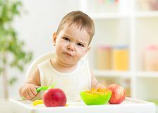 Displeased kid boy with healthy food at kitchen Royalty Free Stock Images