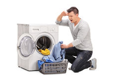Displeased man emptying a washing machine. Studio shot of a displeased young man emptying a washing machine and looking at the clothes isolated on white royalty free stock photography