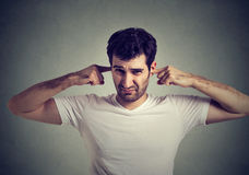 Displeased man plugging ears with fingers doesn`t want to listen Stock Photography