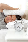 Displeased man putting his head under the pillow. While his alarm clock ringing Stock Photo