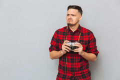 Displeased man in shirt holding retro camera. And looking away over gray background Stock Image