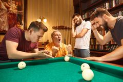 The displeased men playing billiards at office after work. The displeased men playing billiards at office or home after work. Business colleagues involving in Royalty Free Stock Photography