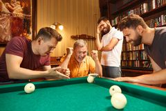 The displeased men playing billiards at office after work. The displeased men playing billiards at office or home after work. Business colleagues involving in Stock Images