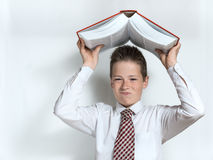 Displeased schoolboy throws big book Stock Photos