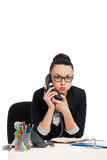Displeased secretary talking on the phone sitting over table Royalty Free Stock Image