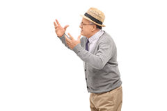 Displeased senior arguing with someone. Studio shot of a displeased senior man arguing with someone isolated on white background stock photo