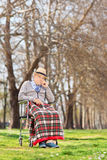 Displeased senior sitting in a wheelchair in park Stock Photography