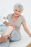 Displeased senior woman getting her leg examined Royalty Free Stock Photo