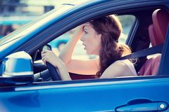 Displeased stressed female car driver. Side view window portrait displeased stressed angry off woman driving car annoyed by heavy traffic street background stock photos