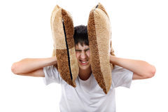 Displeased Teenager with Cushion. Displeased Teenager covering his Ears with Cushion Isolated On The White Background stock images