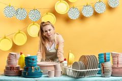 Displeased unhappy housewife standing behind the kitchen table royalty free stock photos