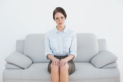 Displeased well dressed woman sitting on sofa Stock Photos