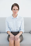 Displeased well dressed woman sitting on sofa Stock Image