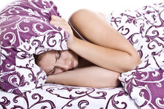 Displeased woman covering ears with pillow Royalty Free Stock Image
