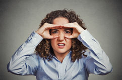Displeased woman looking through fingers like binoculars Royalty Free Stock Photos