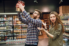 Displeased woman showing at man with keg of beer. Displeased women showing at the men with keg of beer in hands Royalty Free Stock Photography