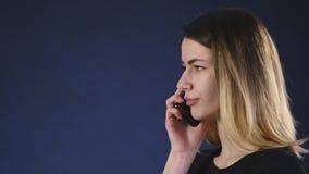 Displeased woman speaks on the phone stock video