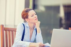 Displeased worried business woman sitting in front of laptop computer. Portrait young stressed displeased worried business woman sitting in front of laptop royalty free stock photo
