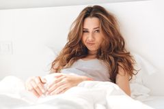 Displeased woman looking camera while lying in bed. Displeased yong woman in pajamas looking camera while lying in bed in the morning royalty free stock photo