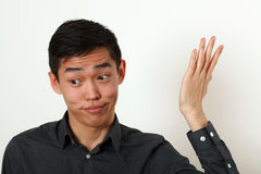 Displeased young Asian man gesturing with his hand Royalty Free Stock Photography