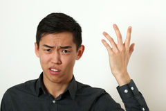 Displeased young Asian man gesturing with his hand Royalty Free Stock Photos