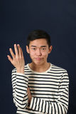 Displeased young Asian man gesturing with one hand Stock Photos