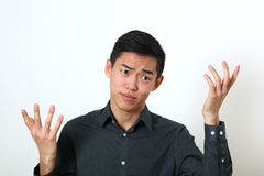 Displeased young Asian man gesturing with two hands Royalty Free Stock Photos