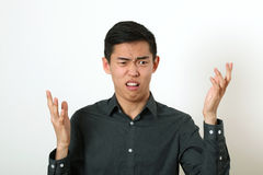 Displeased young Asian man gesturing with two hands.  stock photo