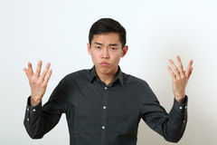 Displeased young Asian man gesturing with two hands Royalty Free Stock Photo