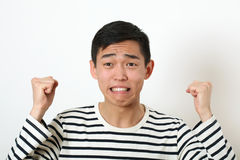 Displeased young Asian man shaking two fists Royalty Free Stock Image