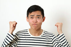 Displeased young Asian man shaking two fists Stock Photo