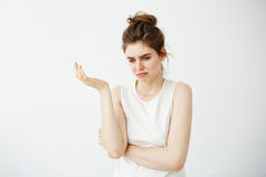 Displeased young beautiful girl with bun gesturing over white background. Stock Photo