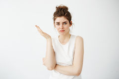 Displeased young beautiful girl with bun gesturing over white background. Royalty Free Stock Photos