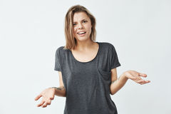 Displeased young beautiful girl looking at camera gesturing over white background. Royalty Free Stock Image