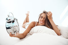 Displeased young beautiful girl lying on bed, looking at alarm-clock. Royalty Free Stock Photo