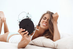 Displeased young beautiful girl lying on bed, looking at alarm-clock. Royalty Free Stock Photos