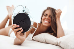 Displeased young beautiful girl lying on bed, looking at alarm-clock. Stock Image