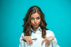 The displeased young business woman with pen and tablet for notes on blue background Royalty Free Stock Photo