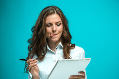 The displeased young business woman with pen and tablet for notes on blue background. Displeased young business woman with pen and tablet for notes on a blue Stock Photos