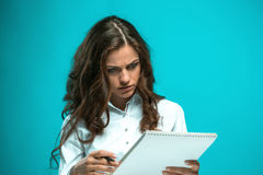 The displeased young business woman with pen and tablet for notes on blue background. Displeased young business woman with pen and tablet for notes on a blue Royalty Free Stock Photos