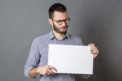 Displeased young businessman claiming on protest sign. Protest sign - displeased young businessman with beard and eyeglasses claiming on a blank banner for copy Stock Image