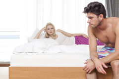 Displeased young couple on bed in hotel room Stock Image