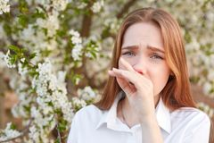 Displeased young female has running nose, feels allergic to seasonal flowers during spring, dressed in white shirt, cant have walk stock image