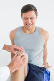 Displeased young man getting his knee examined Royalty Free Stock Photo