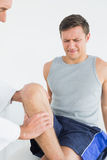 Displeased young man getting his leg examined Stock Image