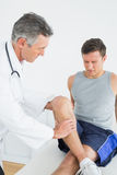 Displeased young man getting his leg examined Royalty Free Stock Image