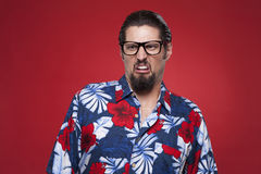 Displeased young man in Hawaiian shirt against red background Royalty Free Stock Photography